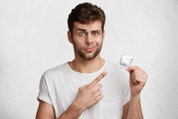 Displeased handsome man with stubble wears casual white t shirt, holds rubber condom in hands, advertizes its quality. Pleasant looking unshaven stylish young male being against of contraceptives