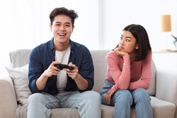 Displeased Japanese Girlfriend Looking At Infantile Boyfriend While He Playing Video Game Sitting On Sofa At Home. Male Emotional Immaturity, Gaming Addiction. Computer Games And Waste Of Time Concept