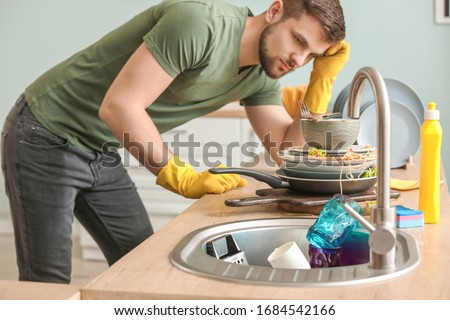 Displeased man looking at pile of dirty dishes in kitchen