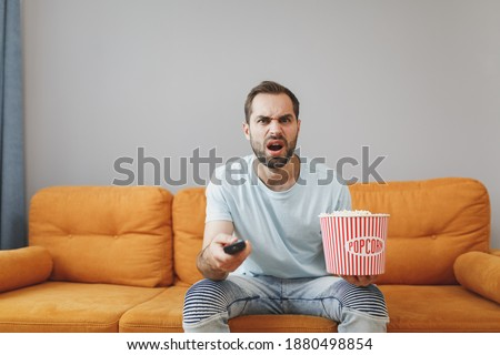 Photo of  Displeased perplexed puzzled young bearded man wearing casual blue t-shirt watching movie film, holding bucket of popcorn and TV remote sitting on couch resting spending time in living room at home