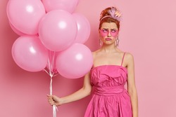 Displeased redhead woman dressed in nineties style outfit wears heart shaped sunglasses holds inflated balloons going to celebrate festive occasion isolated over pink background. Partying concept