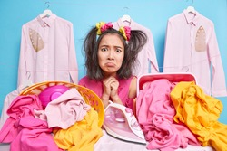 Displeased young Asian woman has sulking expression looks frustrated at camera poses near much laundry in baskets feels tired uses electric iron has two combed pony tails isolated over blue background