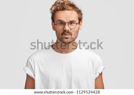 Displeased young Caucasian male frowns face in discontent, has angry expression, being dissatisfied with service in restaurant, going to leave negative comment, poses against white background. #1129524428