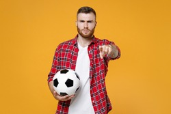 Displeased young man football fan in red shirt cheer up support favorite team with soccer ball pointing index finger on camera isolated on yellow background. People sport leisure lifestyle concept