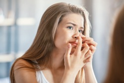 Displeased young woman squeezing acne on her nose while looking in mirror at home