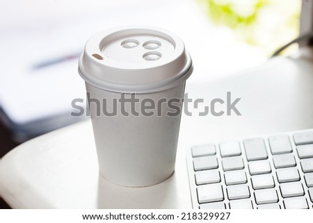 Disposable coffee cup on table near computer keyboard