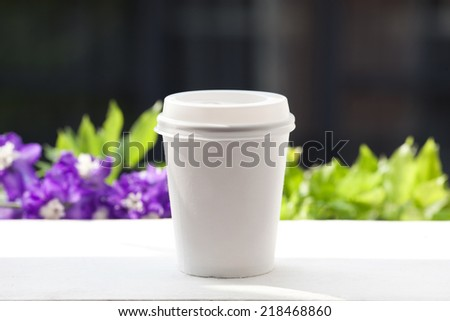 Disposable coffee cup on windowsill with a city in background.