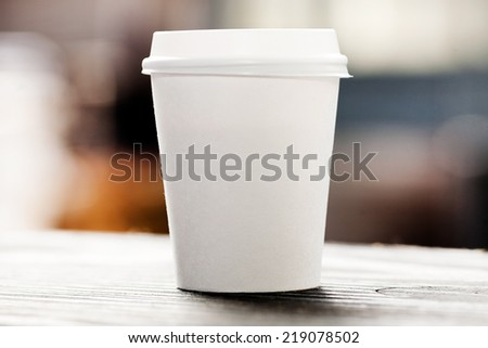 Disposable coffee cup on windowsill with city in background.