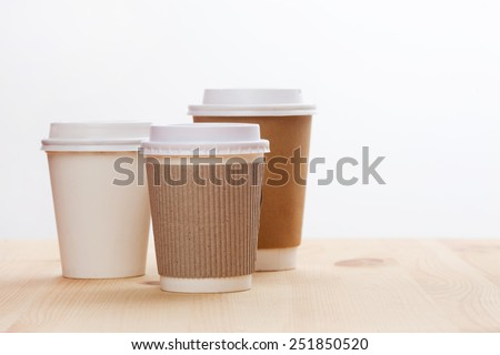 Disposable coffee cups on wooden table.