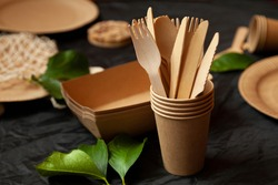 disposable eco tableware made of cardboard spoon fork knife. Place for signature on a black background