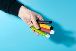 Disposable electronic cigarettes in hand closeup on a blue background with shadows. The concept of modern smoking, vaping and nicotine. Copy space