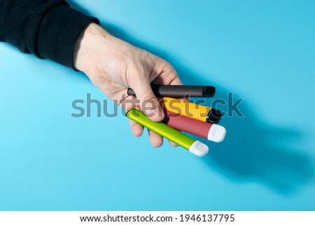 Disposable electronic cigarettes in hand closeup on a blue background with shadows. The concept of modern smoking, vaping and nicotine. Copy space Stock photo ©