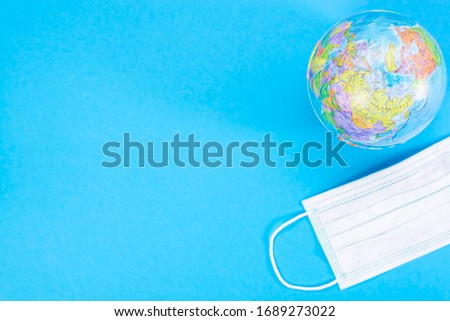 Disposable medical mask and globe on a blue background, pandemic concept. KOVID-19, coronavirus. The global epidemic of the disease Stok fotoğraf ©