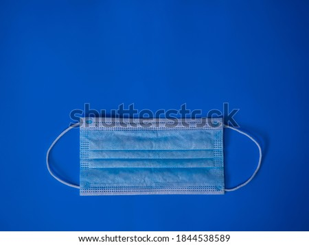 Photo of  Disposable medical mask on a blue background. Covid-19 protection. Health concept.