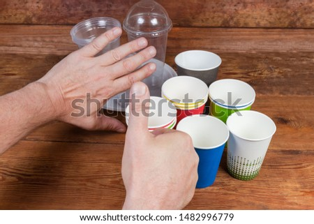 Disposable paper cups and plastic tableware on rustic table. Hand gestures approving to use disposable paper cups and renounce plastic tableware, concept #1482996779