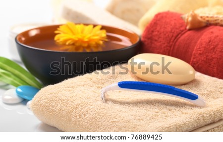 Disposable plastic shaver on towel with soap with other bath utensils in the back (Selective Focus, Focus on the shaver)