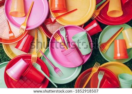 Disposable plastic tableware - plates, forks, spoons. Colored plastic disposable tableware on green grass moss background. Top view. Copy space. Birthday picnic utensil. Recycling plastic and ecology.