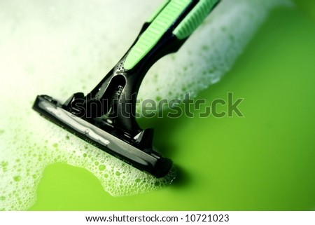 disposable razor against a green background