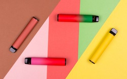 Disposable single pink e-cigarettes with saline nicotine. Pod systems of different colors. Devices for quitting smoking. Red, yellow, green, pink. conceptual fashion photo. Lines and geometry