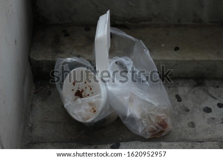 Disposable styrofoam food containers, food packaging, foam bowl trash in plastic bag on the floor.