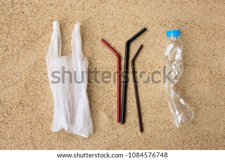 Disposable water bottle, straws and carrier bag, single use plastic item, on sandy beach background. Plastic pollution affecting marine ecology. Environment concept. Top view.