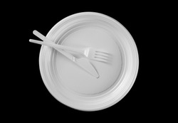 Disposable white plastic plate with knife and fork clipping path, isolated on black background, top view