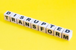Disruption Concept.The word of DISRUPTED and TRANSFORM on wooden blocks.