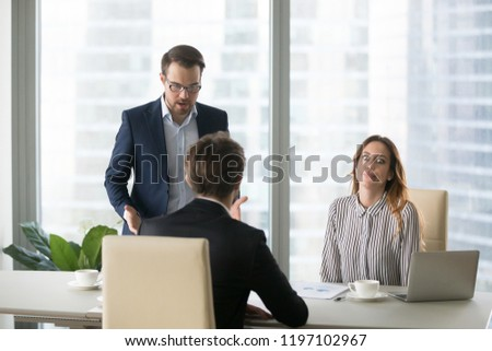 Dissatisfied man shouting at employee, trainee, blaming. Boss scolding subordinates for bad results in report. Executive director is dissatisfied with work of incompetent worker.