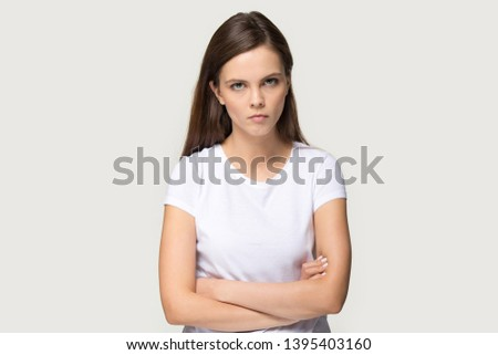Dissatisfied millennial brown haired woman arm crossed looks at camera posing on grey background, disgruntled girl wearing white t-shirt irritated face expressions show negative attitude concept image