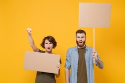 Dissatisfied protesting two people guy girl hold protest signs broadsheet blank placard on stick clenching fist isolated on yellow background. Protests strikes pickets concept. Youth against city