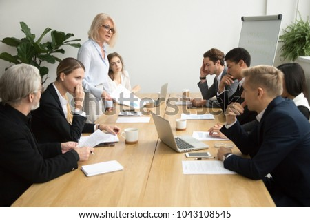 Dissatisfied senior woman boss scolding employees for bad work at diverse group meeting, angry female executive team leader reprimanding subordinates for poor financial result at office briefing