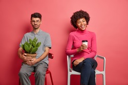 Dissatisfied sullen man poses on chair smirks face holds pot of cactus poses on chair near her dark skinned friend who sits next with coffee isolated over pink background. Mixed race couple indoor