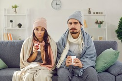 Dissatisfied young couple having problem with central heating, sitting on sofa at home, freezing, drinking hot tea trying to warm up. Sick man and woman wrapped in blankets suffering from cold or flu
