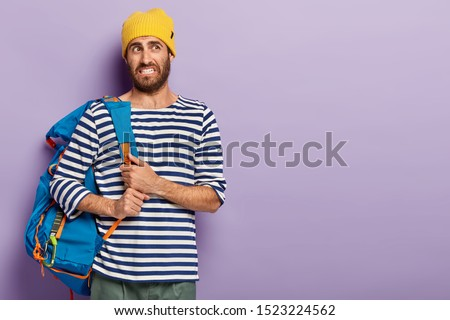 Dissatisfied young man with stubble, feels tired after long walk on foot, wears yellow headgear and sailor sweater, clenches teeth, looks unpleasantly, poses against purple wall, blank space on right