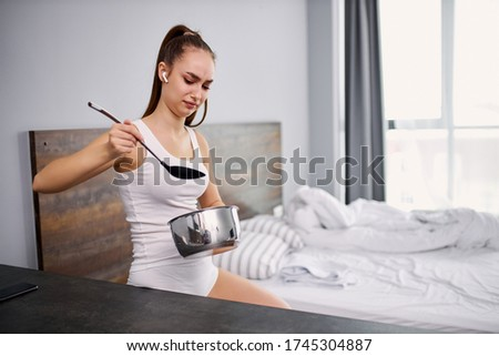 dissatisfied young woman did not liked food in pan, she holds ladle and pan in hands, stands with crouched face