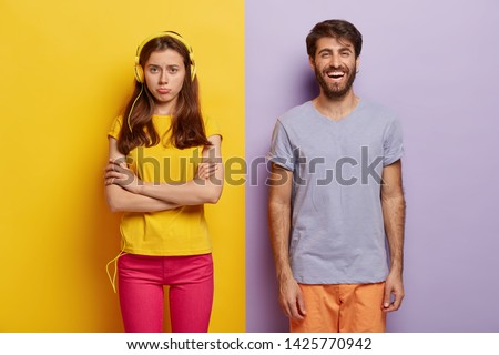 Dissatisfied young woman keeps arms folded, offended after quarrel with boyfriend, ignores live communication, listens music in headphones, happy guy laughs at something funny, dressed casually
