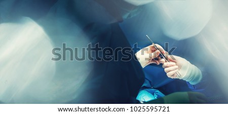 Dissection forceps or hemostatic forceps passing in surgeon hand by team surgeons in surgery center for interventions with instruments in surgeon operation electrosurgery with thoracotomy microsurgery