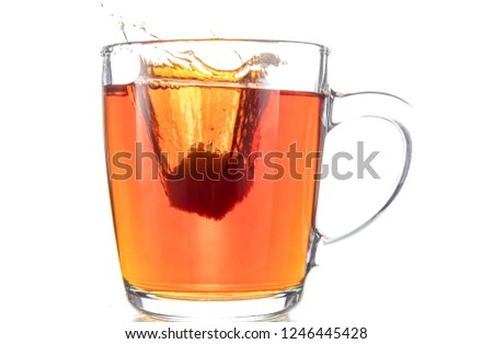 Dissolving a piece of sugar in tea in a transparent mug on a white background, a storm in a glass