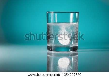 Dissolving  an effervescent tablet in a glass of water at blue background with copy space