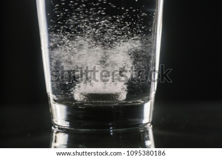 dissolving effervescent tablet in a glass of water