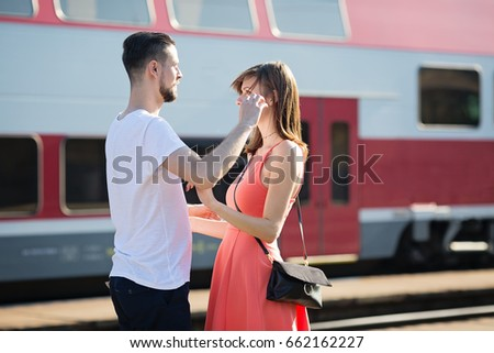 Distance brings sadness when saying goodbye to your loved ones, caucasian young couple saying goodbye at train station during sunny summer day #662162227