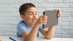 Distance education.Cheerful caucasian child boy is using a laptop and communicates on the Internet at home. Homeschooling, distant learning, online education, video call