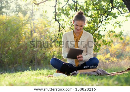 Distance Education. Sitting Woman Using Tablet During Autumn Fun Outdoors
