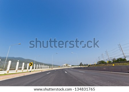 Distance Highway Road with Background of Blue Sky in a Bright Day. #134831765
