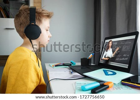 Distance learning, a boy in headphones sits at a table at home looking in a beech laptop. The concept of online education, home education, technology, school