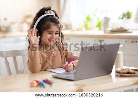 Distance Learning. Cute little home schooler girl having video lesson with laptop in kitchen, studying with computer during coronavirus quarantine, enjoying online education, waving hand at camera