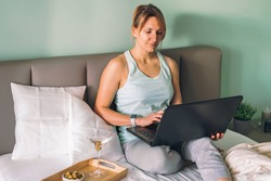 Distance learning online education or work or chating with friends. Happy woman lying in a bed, using laptop and drinking martini.