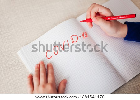 Distance learning online education. The inscription 'Kovid-19' with a red pen in a notebook, which lies on a wooden table. Place for text. View from above. Stok fotoğraf ©
