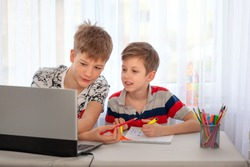 Distance learning online education. Two brothers studying at home with notebook and doing school homework. Concept online education. Stay at home entertainment.