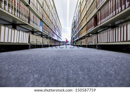 Distance shot of a female in university library with shelves of books in foreground